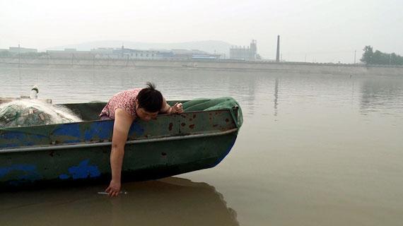 Wei Dongying nimmt Wasserproben aus dem verschmutzten Fluss. Bild: ZDF / © Stef Tijdink