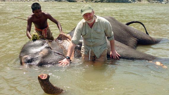 George McGavin und ein Elefant erfrischen sich bei glühender Hitze im Fluss beim Basecamp im Süden Bhutans. Bild: NDR/Mark Roberts/BBC